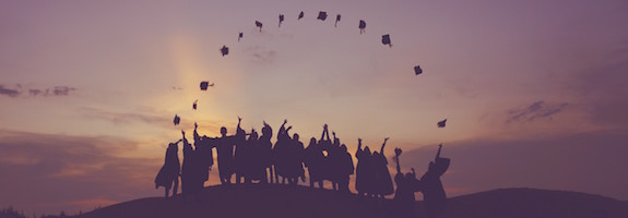 Group of graduates throwing their hats in the air